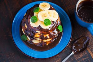 Pancakes with banana, topped with chocolate. Top view
