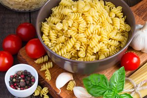 Different kinds of pasta, cherry tomatoes, basil and spices on a