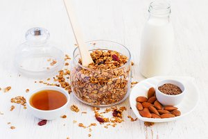 Healthy breakfast - granola, almonds, milk and honey on a white