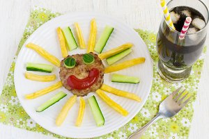 Cutlet, French fries and cucumbers are laid out on a platter in