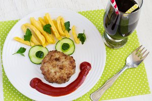 Cutlet, cucumber and French fries in a cheerful faces. Children'