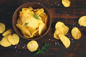 Crispy potato chips in a cup on a dark background, tinted