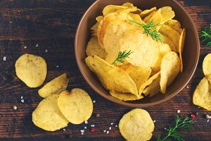 Crispy potato chips with a bowl, top view, tinted