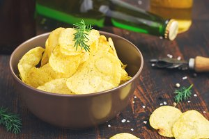 bowl of potato chips with dill on beer background, tinted