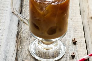 Coffee with ice in a glass on the old background