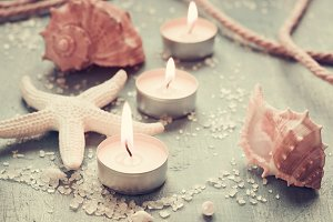 Candles, seashells and starfish on vintage background, monochrom