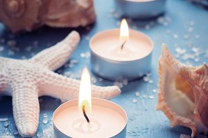 Three burning candles in a row on background of sea objects, tin