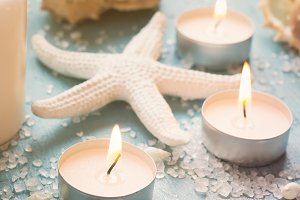 Burning candles and starfish on a blue background, tinted