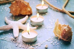 Candles, seashells and starfish on vintage background, tinted