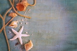 Marine objects - shells, starfish, a rope and salt on blue vinta