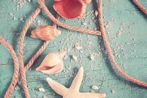 Seashells, starfish and rope on a turquoise background. Postcard