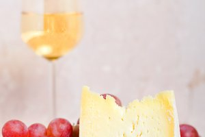 a piece of cheese, wine and grapes