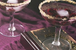 Two alcohol cocktails with berries on purple. Square