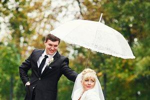 Groom holds an umbrella