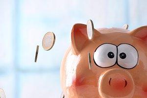 Coins falling on Piggy bank window