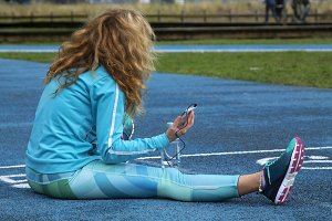 Woman doing sport on track with mobile phone and headset