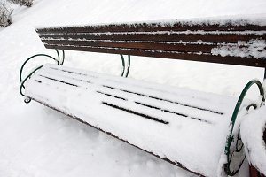 Snow on bench in park of winter