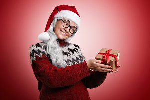 Woman in Christmas sweater and Santa hat with presents