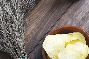 Rustic bowl with chips next to a beer on wooden table