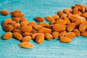 handful of almonds on a blue wooden background