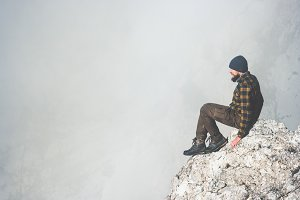 Man on rocky cliff foggy mountains