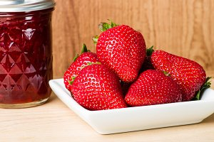Strawberries on white plate with jar