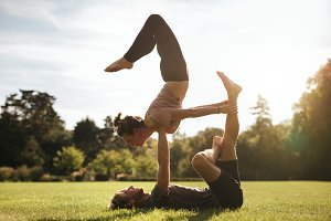 Fit young couple doing acroyoga
