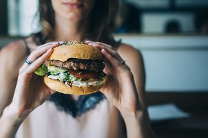 Young girl holding fresh hamburger
