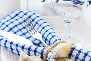 Summer table setting in marine style, decorated with shells and