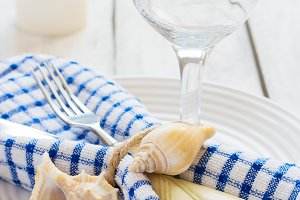 Marine style table setting with candle and seashells