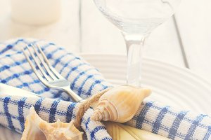 Marine style table setting with candle and seashells, tinted