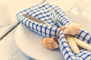 Summer table setting in marine style, decorated with shells, clo