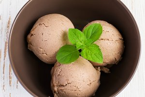 Chocolate ice cream with mint leaf in brown bowl, top view