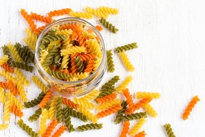 colorful italian fusilli pasta in a jar on a white background. T
