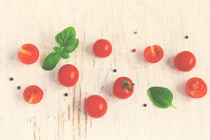 Cherry tomatoes with basil leaves on white Shabby background, ti