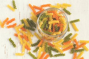 colorful italian fusilli pasta in a jar on a white background, t