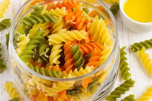 colorful italian fusilli pasta in a jar, cherry tomatoes and spi