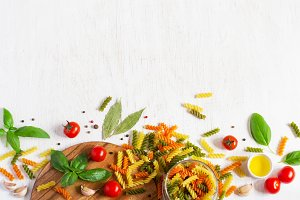 Background with colored paste, cherry tomatoes, spices. The top