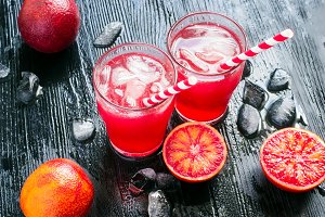 Juice of blood orange with ice in glasses with straws