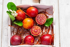 Juicy blood oranges, whole and half, on a white background