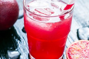 Fresh juice from blood oranges with ice, dark background