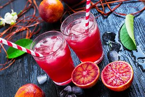 Fresh juice from blood oranges with ice. dark background
