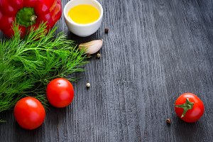 colorful vegetables, olive oil and spices on a dark background,