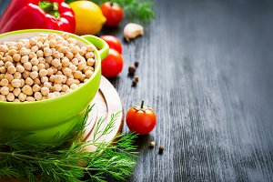 Background with chickpeas and colorful vegetables, space for tex