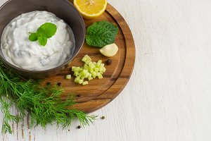 Tzatziki sauce in a bowl and the ingredients, place for text