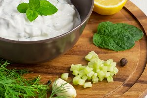 Tzatziki sauce in a bowl and ingredients - cut cucumber, mint, d