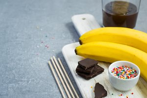 Ingredients for Banana Pops on a white cutting board, space for