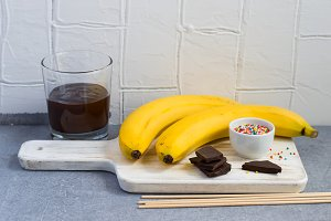 Ingredients for Banana Pops on a white cutting board on a gray b