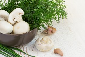 Champignon mushrooms in a bowl with fresh herbs, space for text