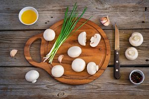 Champignon mushrooms and herbs on a cutting board,  top view, ti